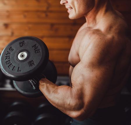 atleta entrenando curl de bíceps para una hipertrofia muscular