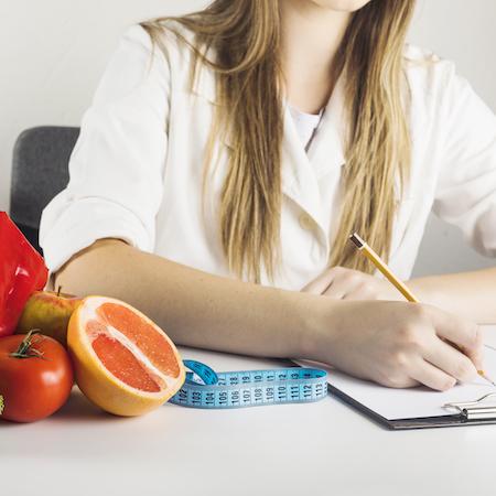 nutricionista en consulta haciendo dieta para perder peso